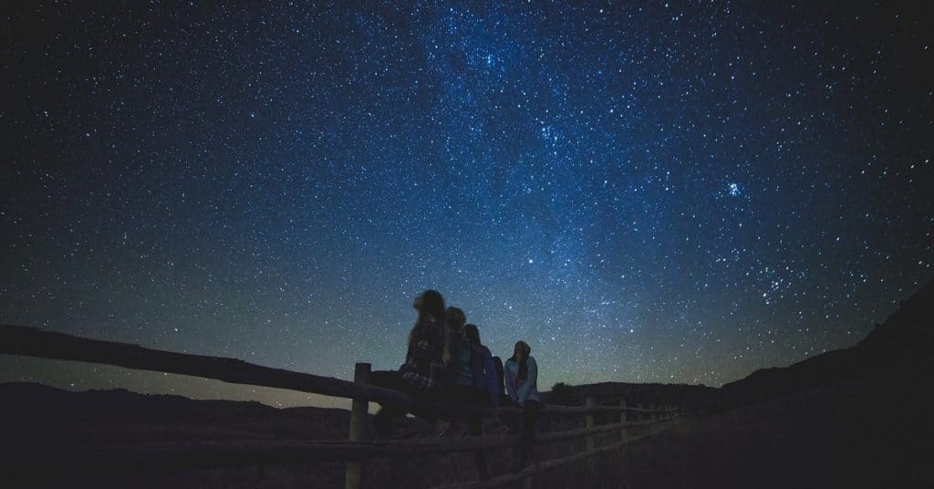 Group of men and women sat on a fence star gazing