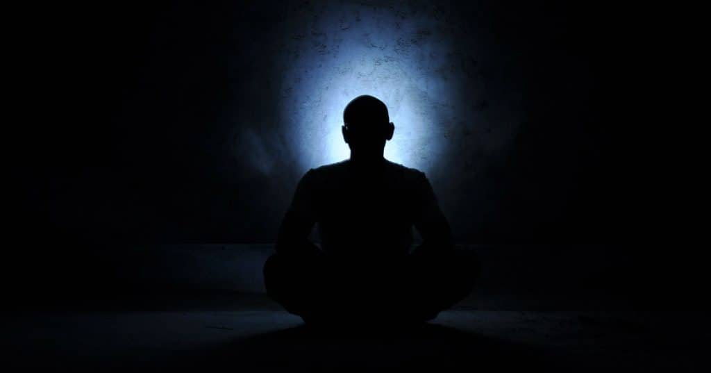 Man meditating with blue background in darkness