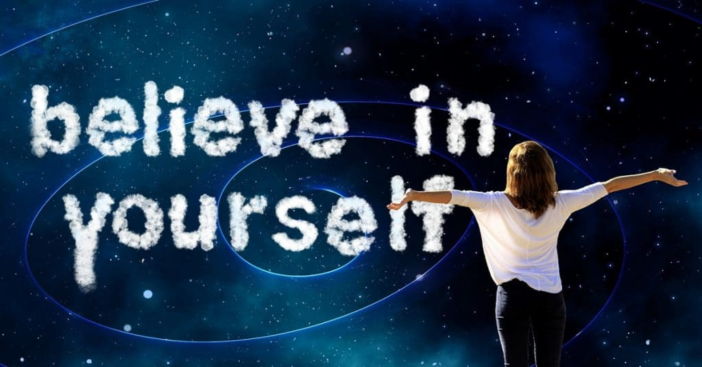 woman with arms out wide with clouds infront of universe saying believe in yourself