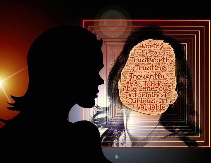 outline of woman looking at face of herself but with affirmations