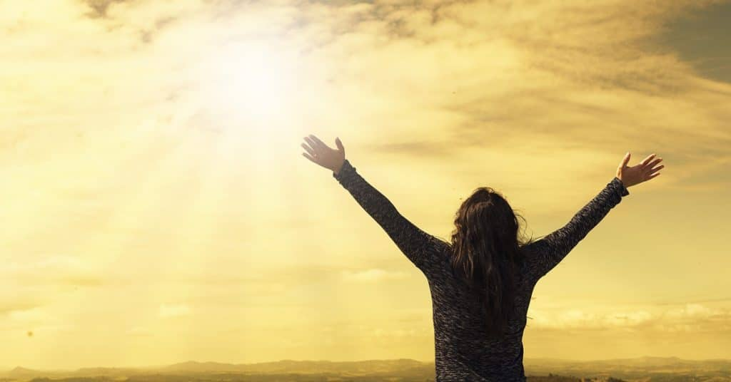 woman with arms up wide in the air looking up to a golden yellow sky with clouds praying